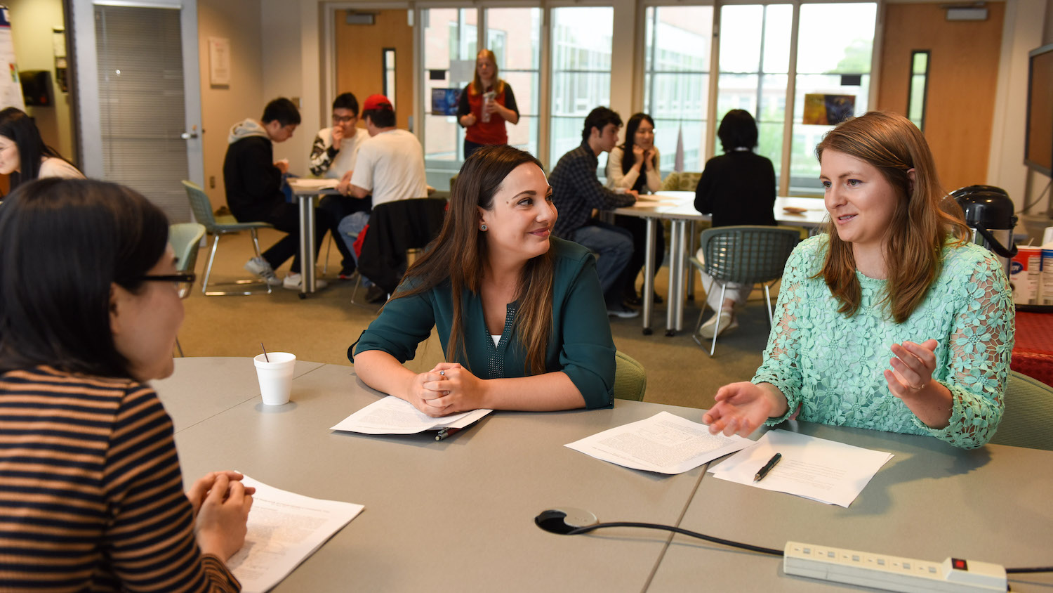 Students and faculty discuss research around a table in a common room