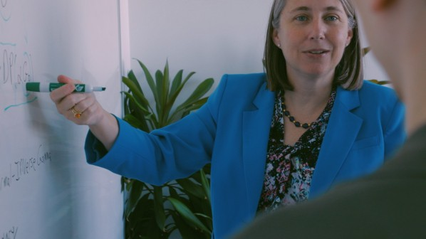 Alyson Wilson points at something on a whiteboard while talking to a collaborator