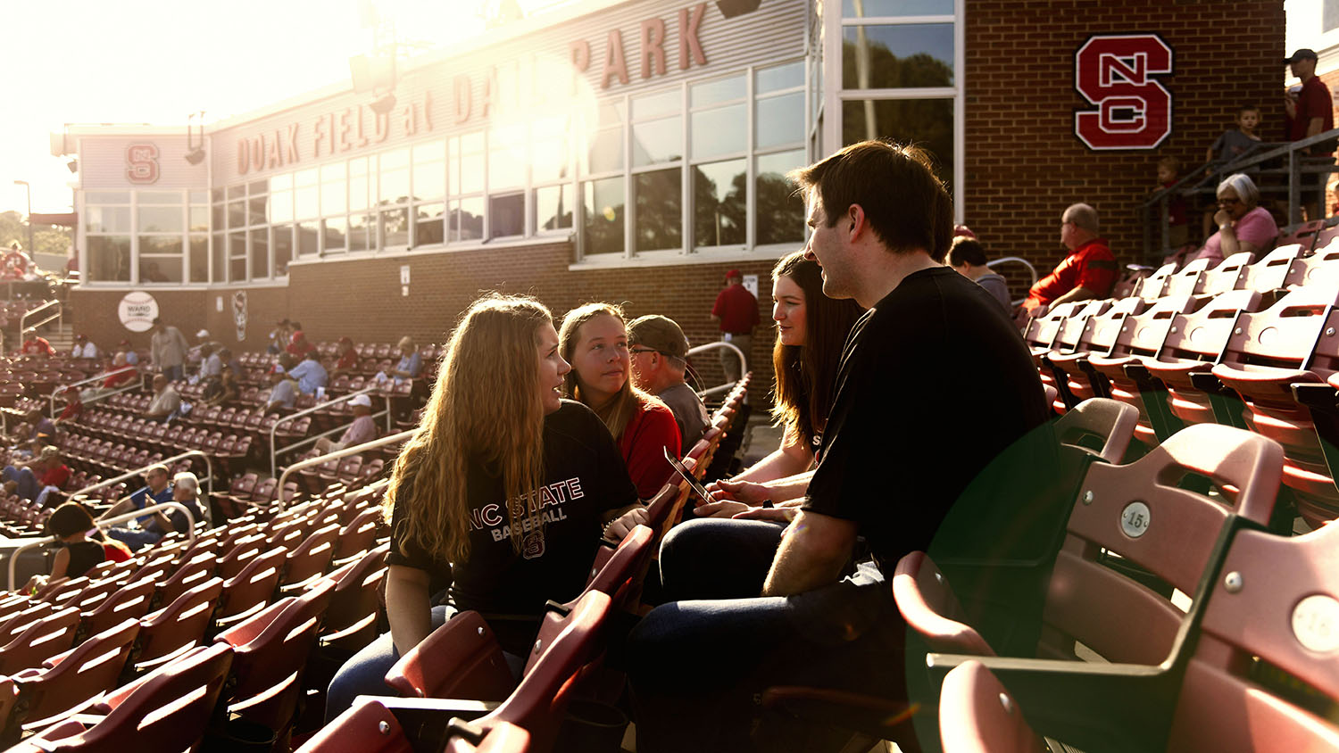 A group of students collaborate in the stands at NC State's Doak Field