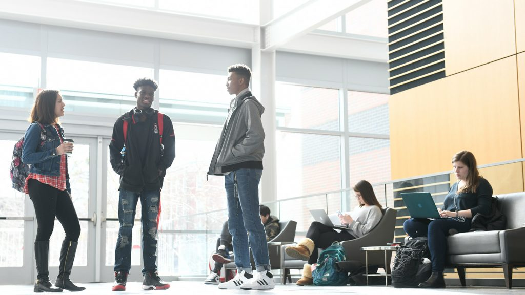 Three students talk in the atrium of SAS Hall while other students work in the background