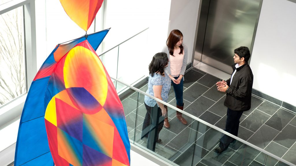 Three people stand in the atrium of SAS Hall with a colorful art installation in the foreground