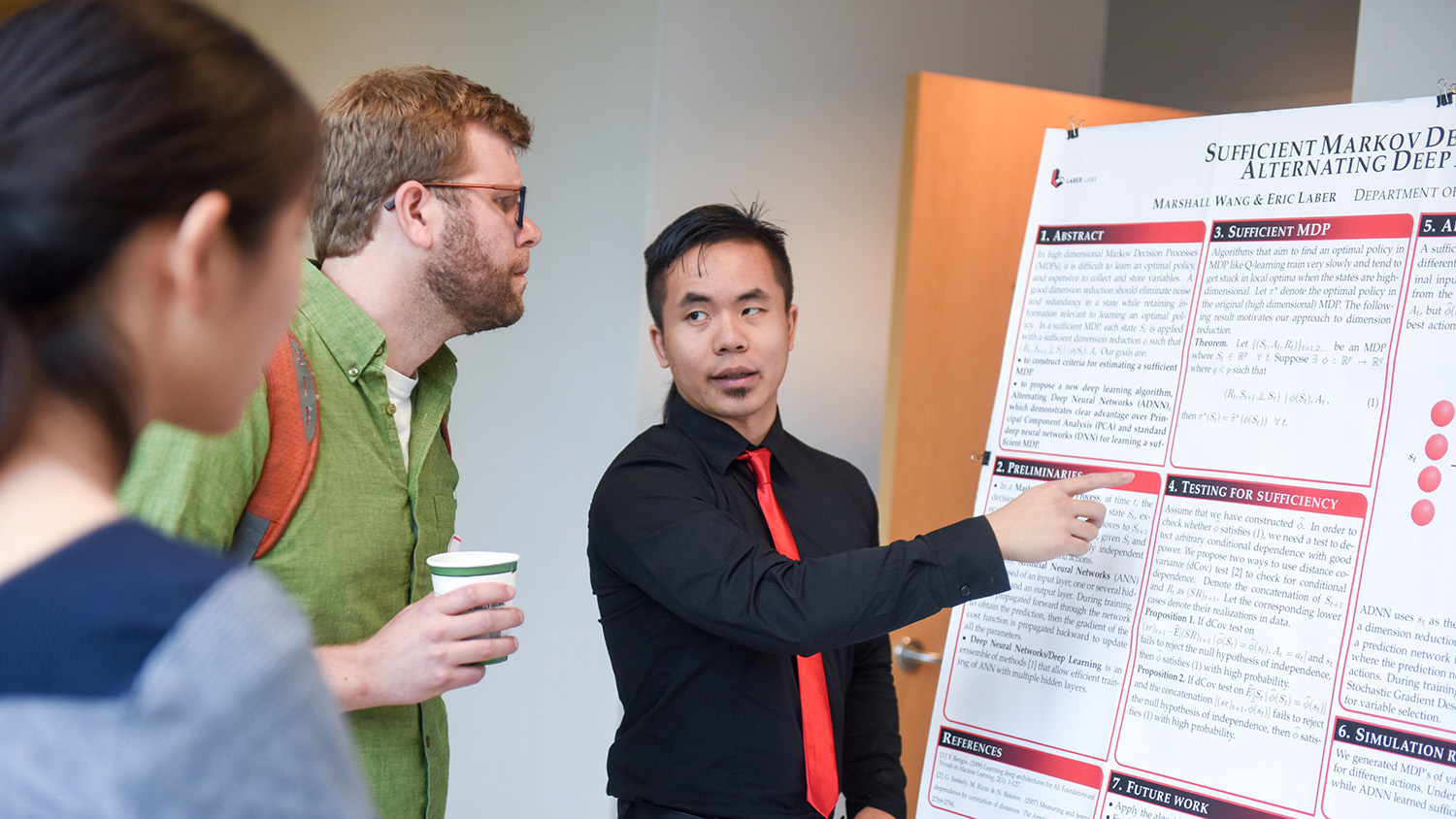 Two people look on as one student explains his research using a poster