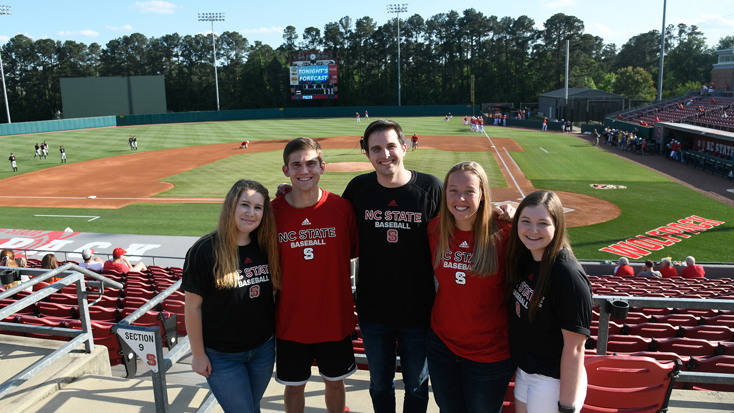Five smiling students in front of NC State's baseball field