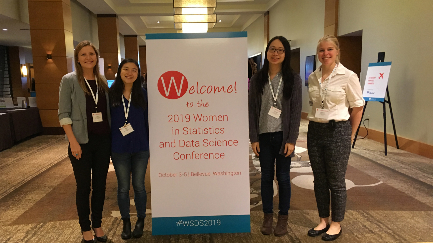 Four students stand on either side of a banner at the 2019 Women in Statistics and Data Science Conference